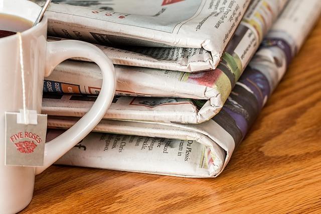 složené noviny a šálek