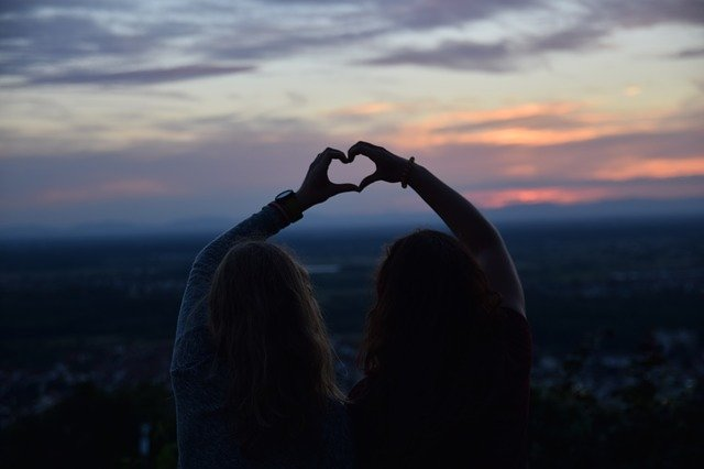 dvě ženy sedí vedle sebe na kopci
